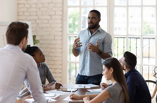 Serious black manager talk to diverse staff people at meeting